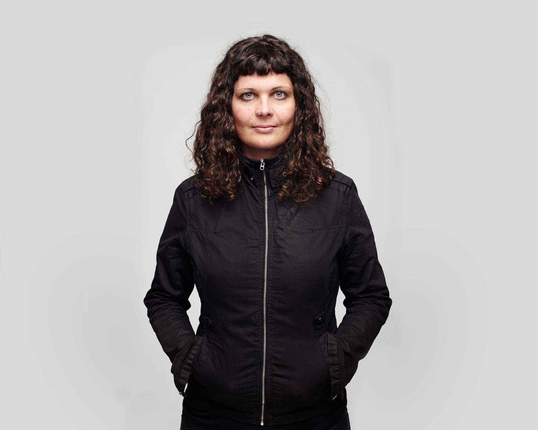 Frau locken Hände in Jackentasche grauer Hintergrund Jörn Strojny