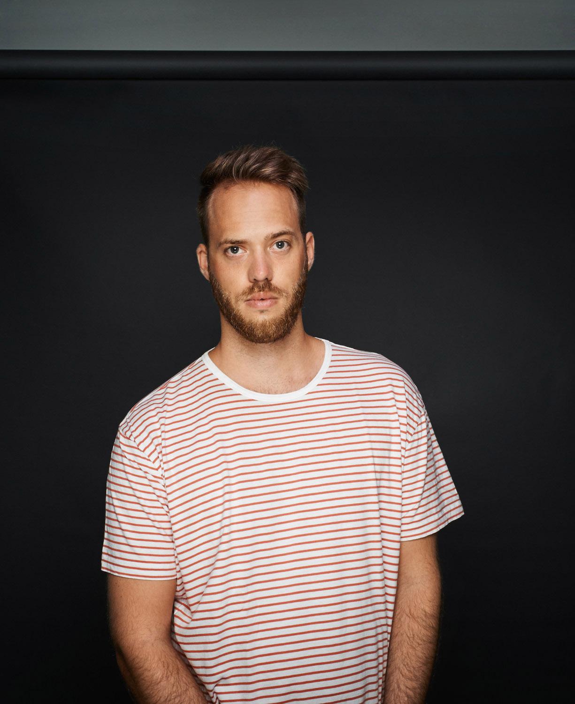 junger Mann bestreiftes grauer Hintergrund Studio streifen lächelnd Jörn Strojny