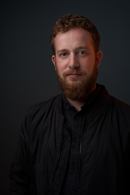Vincent Brinkmann Künstler Portrait Künstlerportrait lächelnd dunkler Hintergrund Studio Jörn Strojny