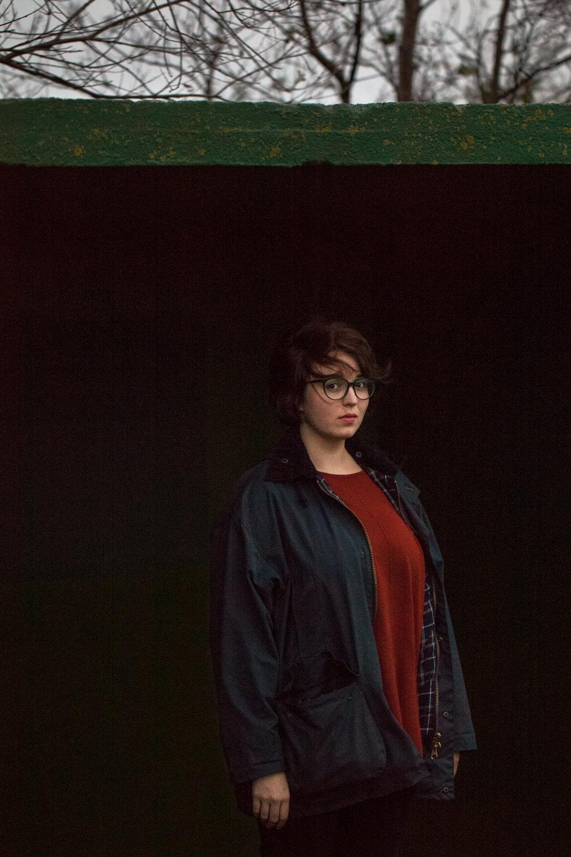 Frau steht draußen vor schwarzem Hintergrund Äste Himmel grüner Balken Jörn Strojny