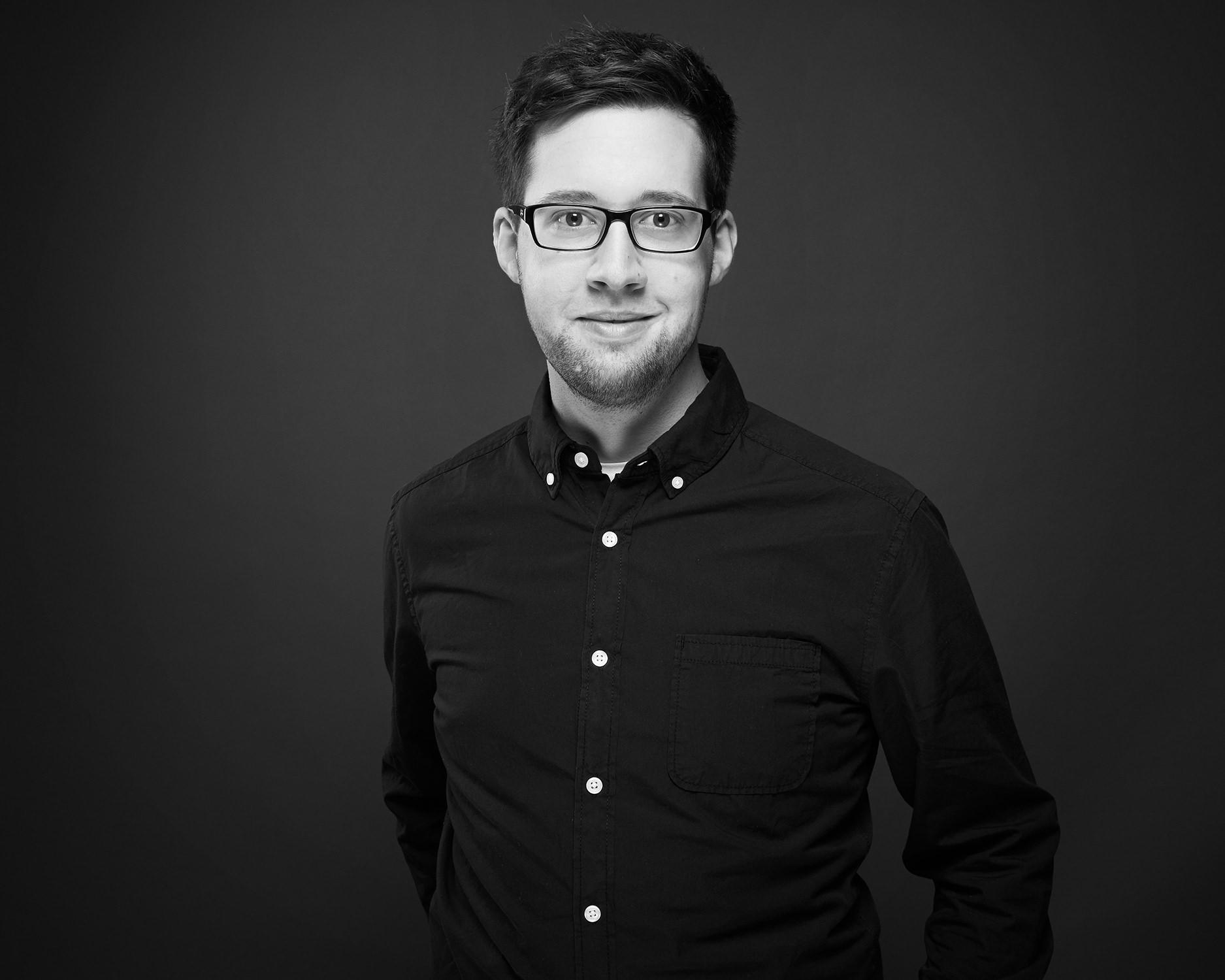 junger Mann Brille Studio Portraitfoto Hemd weiße Knöpfe Jörn Strojny