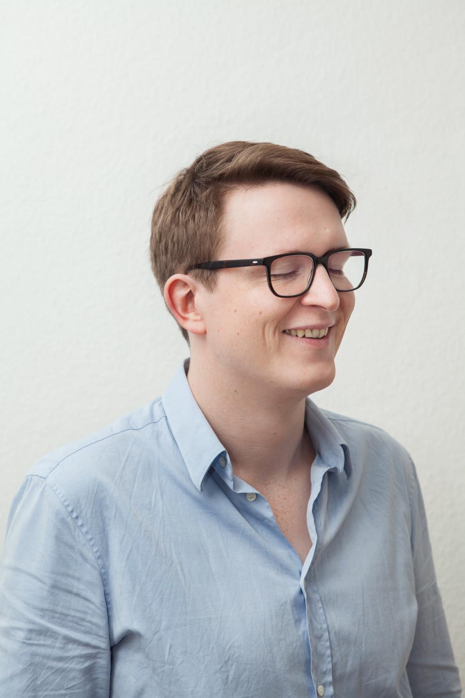 Porträtfotograf lachender Mann geschlossene Augen helle Wand Jörn Strojny