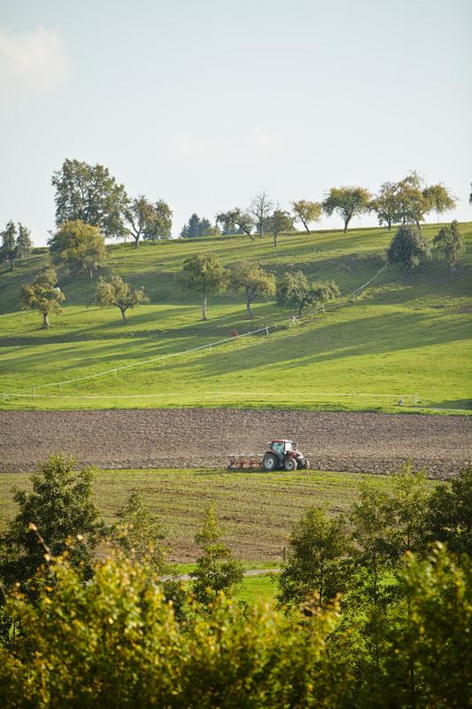 Traktor pflügt Feld in hügeliger Landschaft in Hohenlohe Baden-Württemberg Honhardter Demeterhöfe Jörn Strojny