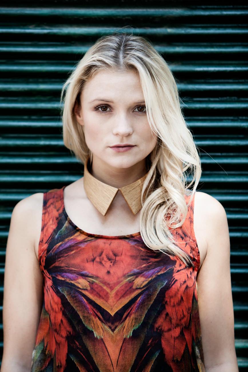 akjumii modekollektion grüner hintergrund portrait holzkragen bunt blond frau mode münchen jörn strojny